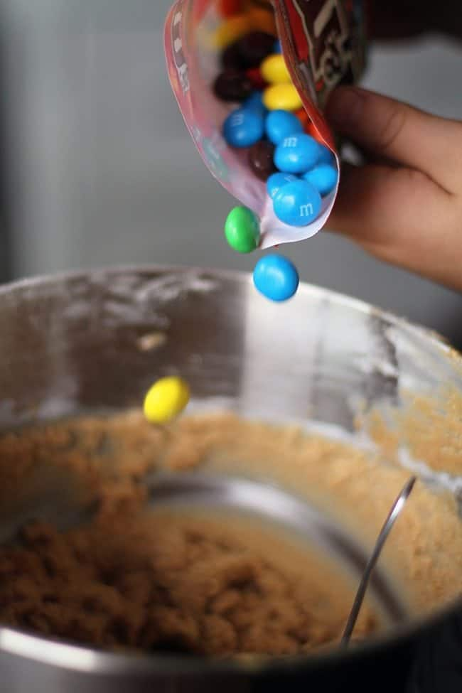 adding bright-colored M&M's to peanut butter cookie dough