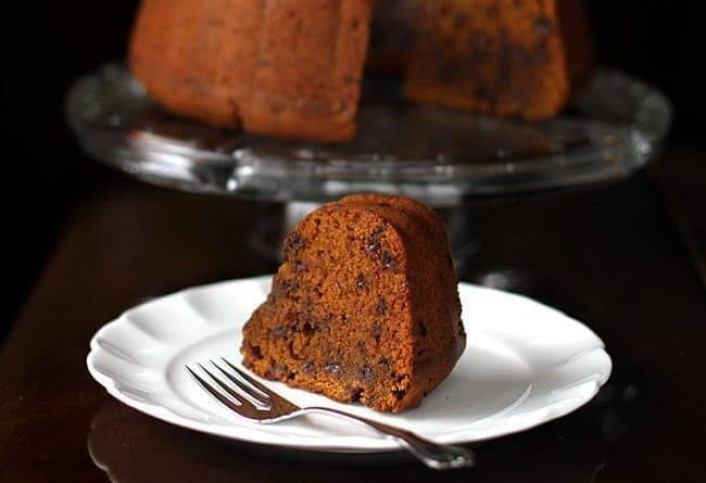 dense and chock full pumpkin Bundt Cake in a cake holder and a slice in white dessert plate with fork