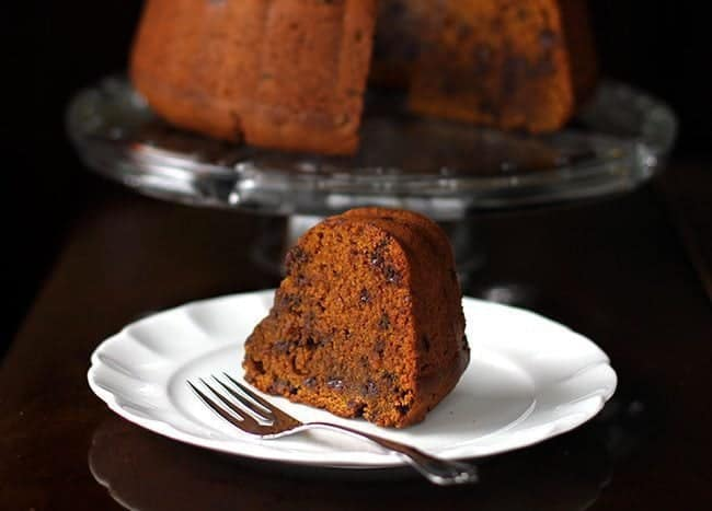 a slice of Chocolate Chip Pumpkin Bundt Cake in a white dessert plate and in a cake holder on background