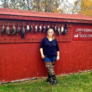 woman standing in front of requisite duck wall where fallen ducks are hanging