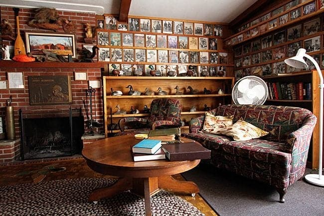 wall space with antiques, duck decoys, photos, paintings and mounted animals