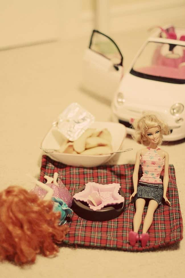 close up of barbie dolls sitting and a plate bowl with Yopa and slices of apple beside it