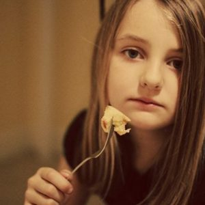 close up of young girl holding a fork with slice of an apple