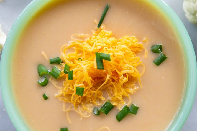 close up Cheesy Cream of Cauliflower Soup in a soup bowl with grated cheddar cheese and chopped green onion