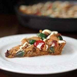 a slice of Christmas Fruitcake Chocolate Chip Skillet Cookie in a white dessert plate