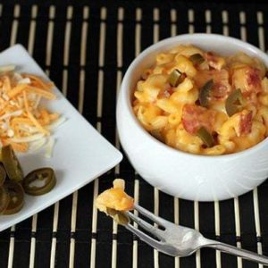 a plate of grated cheese and sliced Jalapeno, and a serving dish with Mac and Cheese