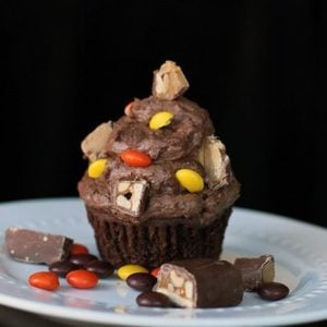 Buttercream Icing with chopped up candy bars on top of chocolate cupcake in a plate