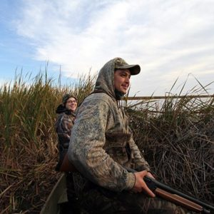 man holding riffle and woman both wearing duck hunting gear in tall grasses
