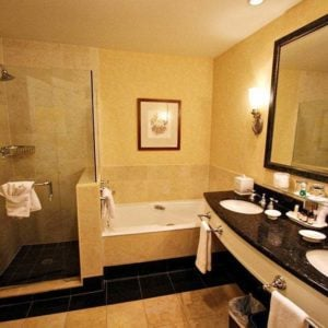 spacious and beautiful bathroom with double sink, glass enclosed shower and a very large soaker tub