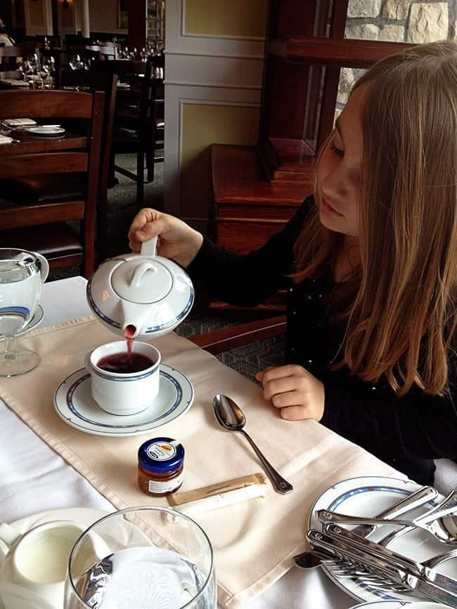 little girl pouring her own hot tea in her white cup