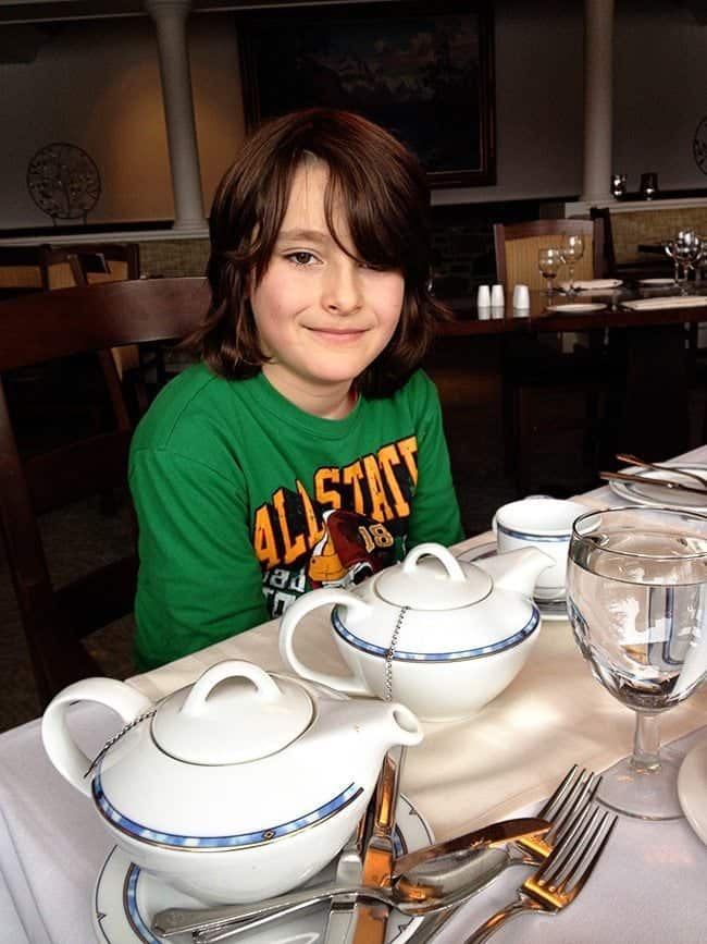 kid in green shirt sitting beside the table while wailing for the tea