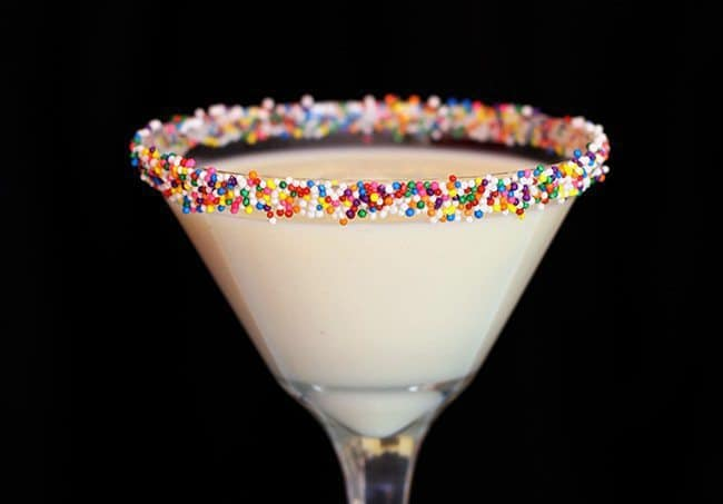 a glass of Eggnog Martini with colorful sprinkles on the rim