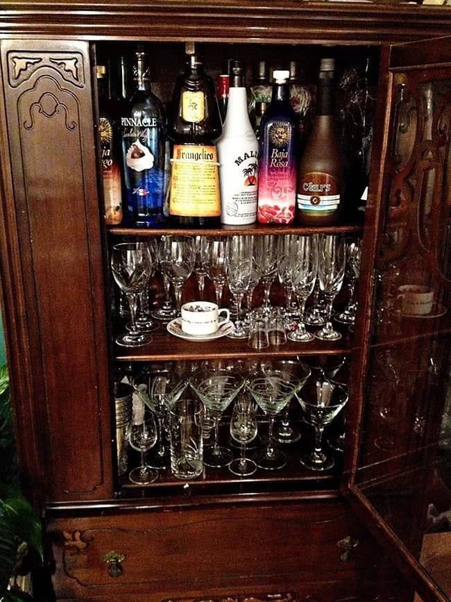 wooden cabinet loaded of liquor and cocktail glasses