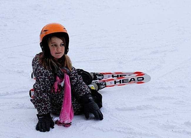 little girl in skiing gear sitting in the snow