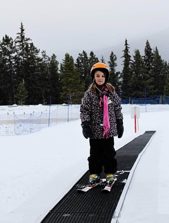 little girl wearing her skiing gear on her skiing board