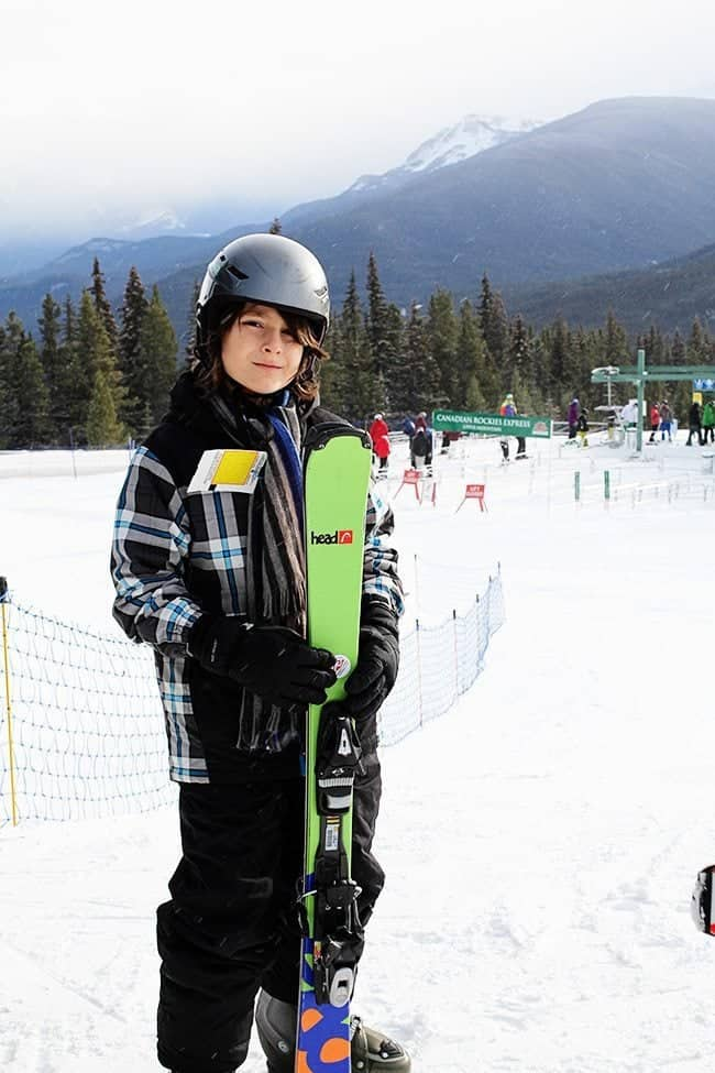 little boy in skiing gear holding his skiing board