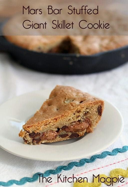 A slice of Mars Bar Stuffed Giant Chocolate Chip Cookie in a White Plate