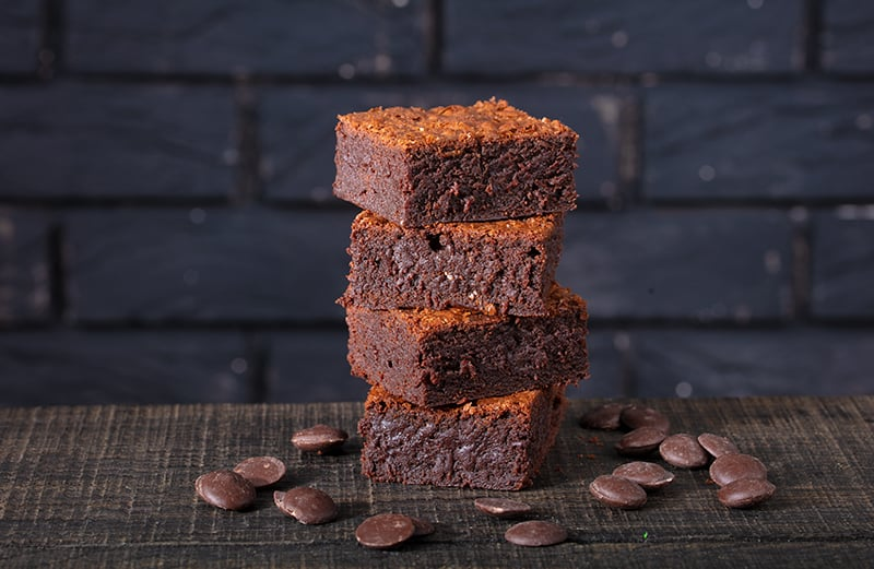 stack of perfectly squared cut brownies with mint chocolate chips around