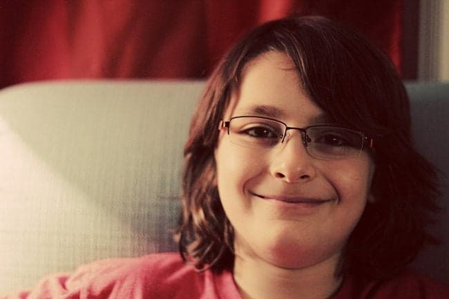 young boy wearing eye glasses, smiling while sitting in the couch