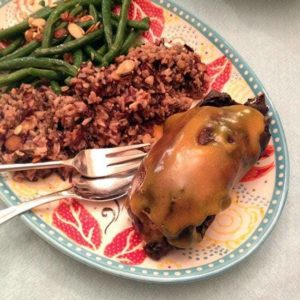 plate with braised wild duck, rice and almond green beans with a delicious orange sauce over it