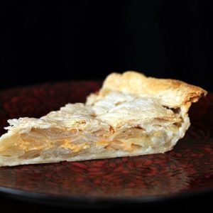 a slice of Scalloped Onion Pie in a red plate