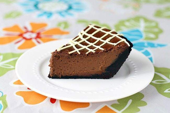 a slice of Chocolate Pumpkin Pie in a white plate on a floral tablecloth background