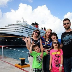 group picture during Merrytime Disney Cruise with the cruise ship at the background