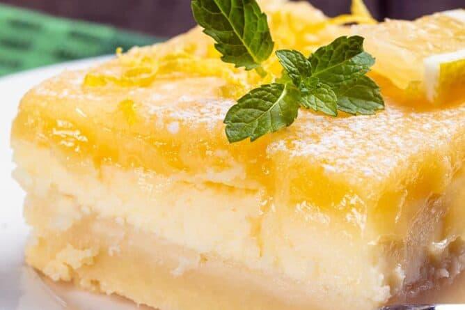 close up white plate with Lemon Cheesecake Bar garnish with lemon balm leaves
