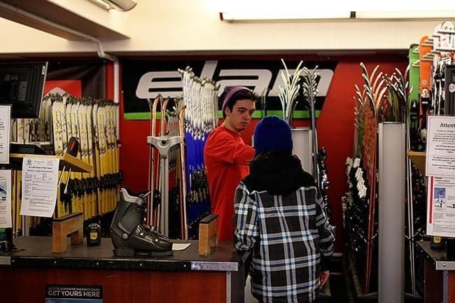 Rental shop staff assisting the kid in choosing skiing gear