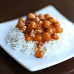 Chickpea Curry on top of rice in a white plate