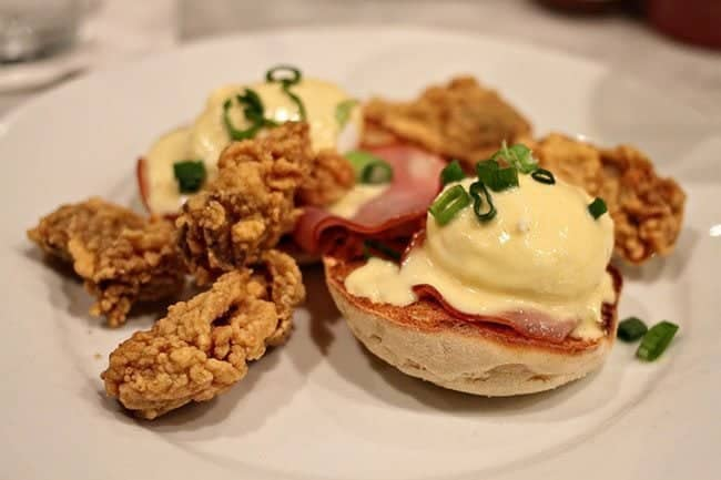Eggs Benedict accompanied by fried cornmeal-crusted oysters with Hollandaise sauce
