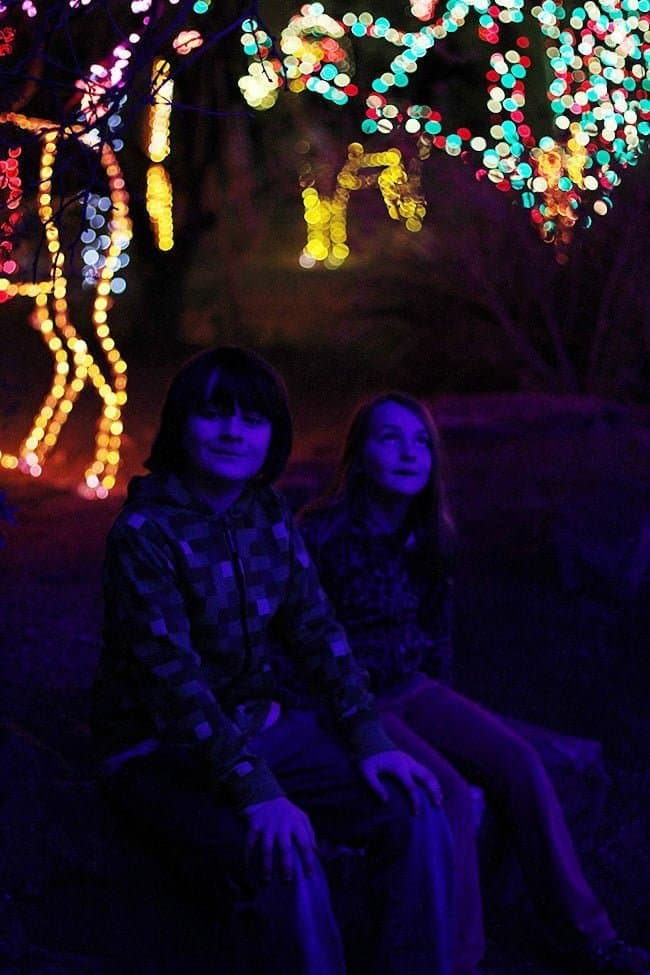 two little children sitting with the background of lighted figure