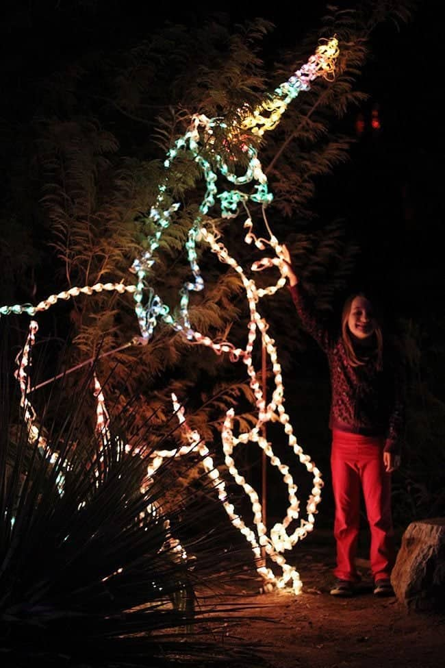 little girl standing on the side of unicorn figure with light