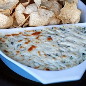 close up of Chips with Cheesy Kale & Artichoke Dip in a Pyrex Bowl