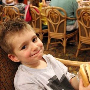 little boy sitting, holding his burger