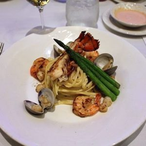 white plate with seafood pasta with a lobster tail, scallops, mussels and shrimp