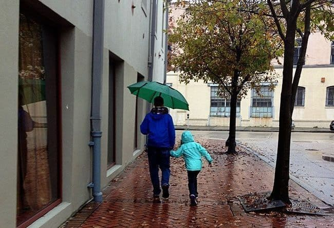 Father and his child walking under the rain with green umbrella