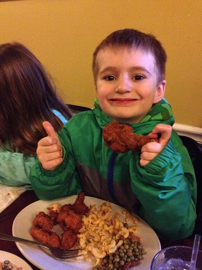 little boy holding a piece of crispy hot chicken at Willy Mae's Restaurant
