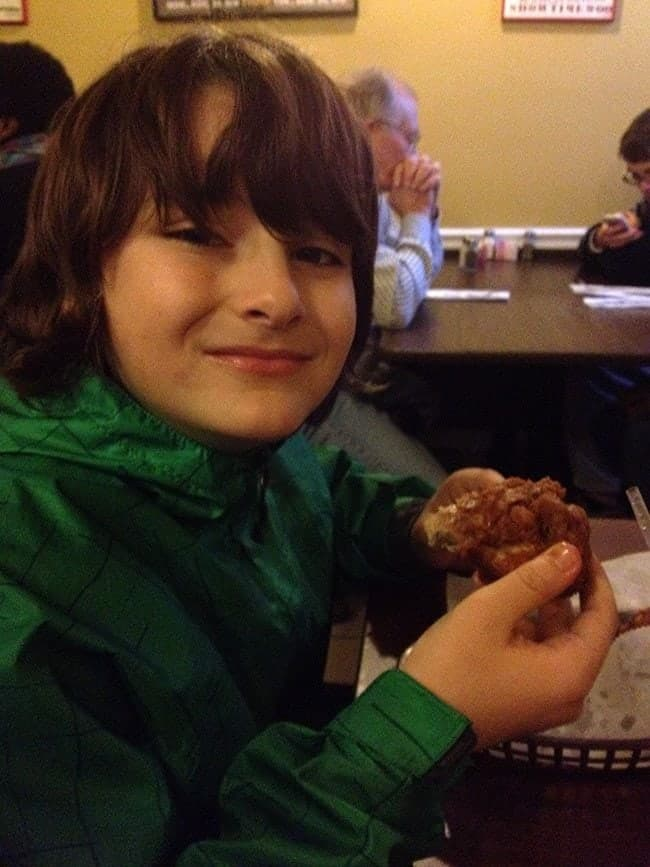 young boy holding a piece of crispy hot chicken at Willy Mae's Restaurant