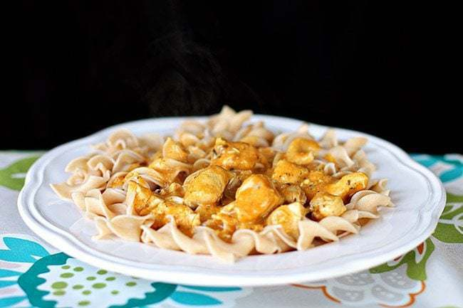 White floral printed tablecloth underneath a plate of Chicken Korma Over Pasta