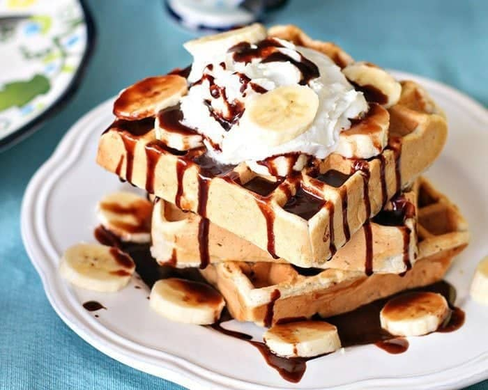 Close up Stack of Banana Waffles in a White Plate, topped with whipped cream, fresh bananas and Nutella sauce