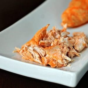 Close up of Crock Pot Buffalo Chicken in a White Rectangular Plate on Black Background