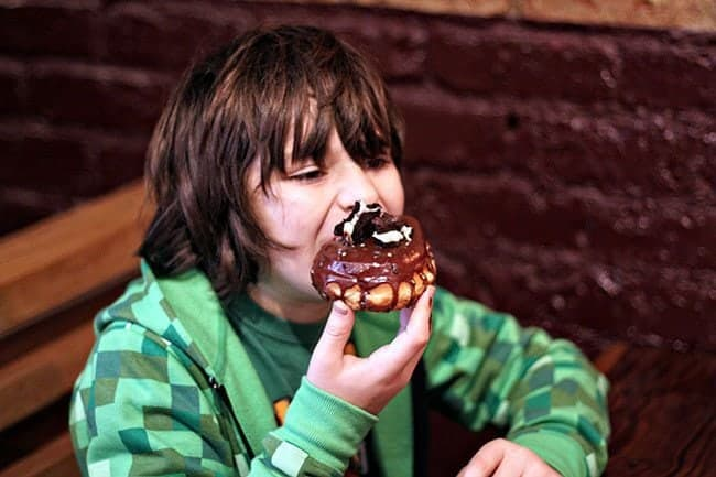 young boy having a bite of his chocolate blackout donut