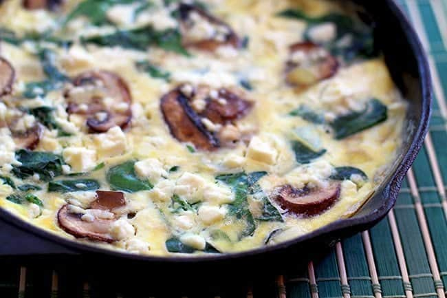 Close up of Spinach Mushroom Frittata in Skillet on a blue green mat