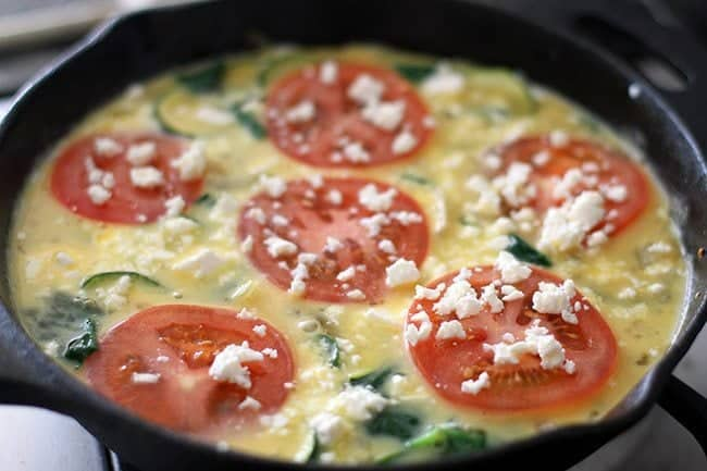 Close up Feta Frittata in a black skillet with Tomato and Spinach