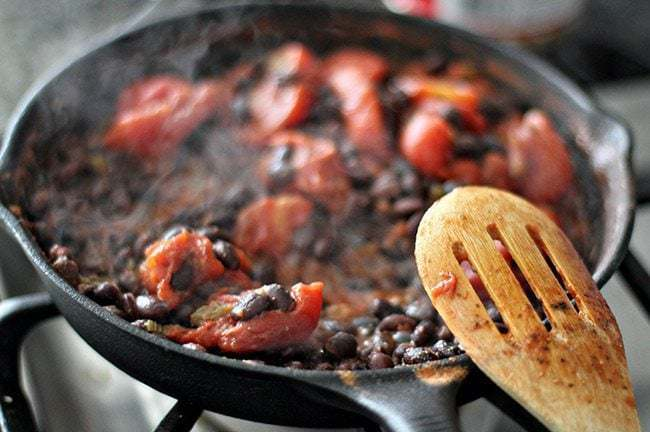 Cooking beans, tomatoes and cumin in skillet