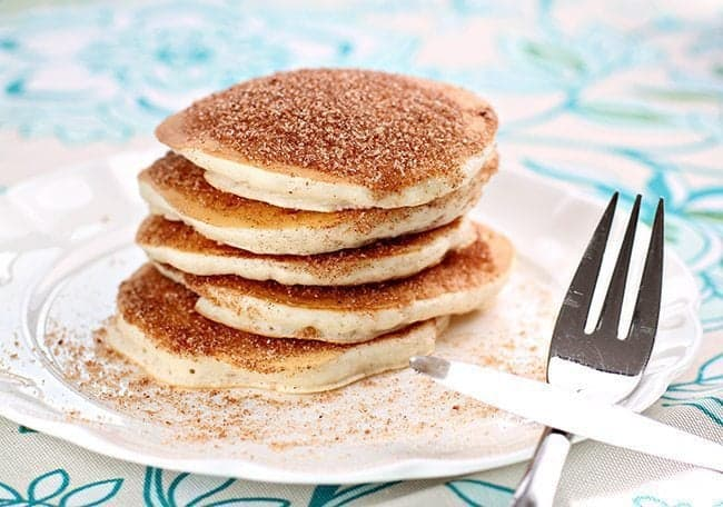 Stack of Snickerdoodle Pancakes coated with sugar and cinnamon mixture in a white plate