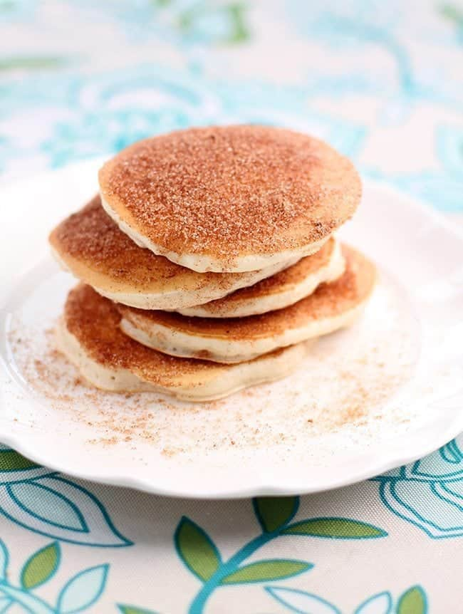 Top down shot of Snickerdoodle Pancakes coated with sugar and cinnamon mixture in a white plate