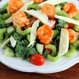 Buffalo Shrimp Kale Salad in white plate topped with celery, cucumber and tomatoes