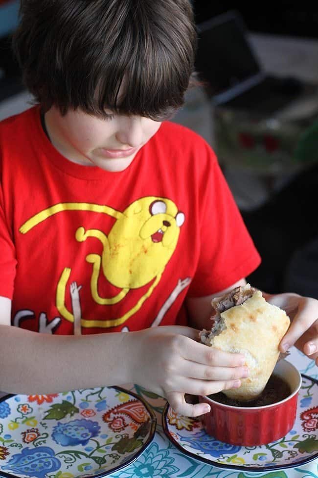 boy wearing red shirt holding sandwich and dipping it to crock pot beef dip